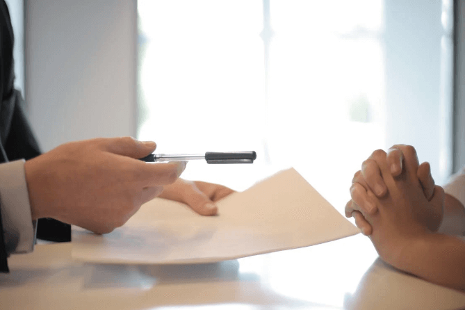 Man-encouraging-woman-to-sign-document